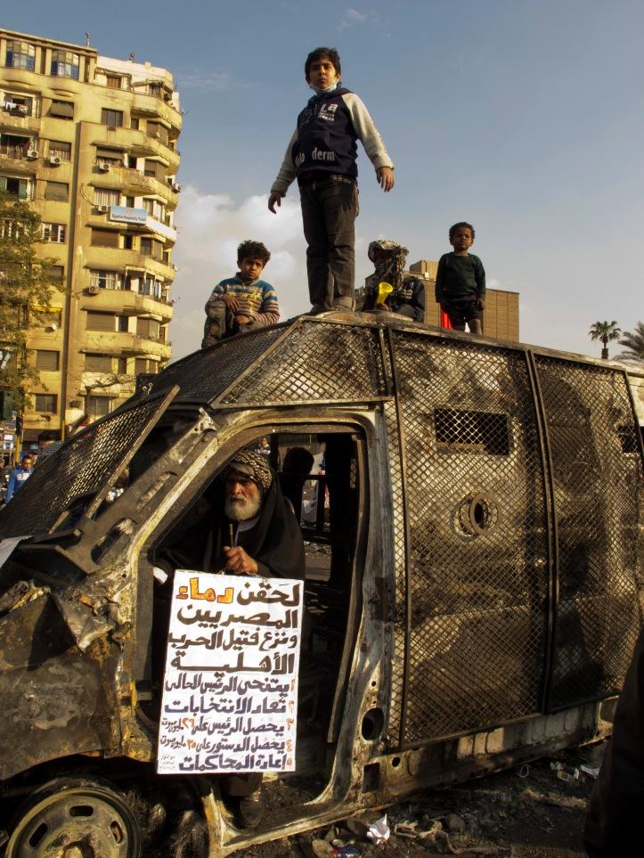 Street Children sopra una camionetta della polizia bruciata durante gli scontri a Tahrir (2012)